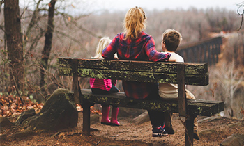 Mum sat on a bench overlooking a valley with her two young children